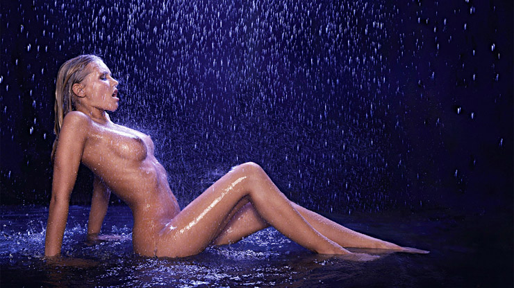 Nude in the rain sitting in a puddle